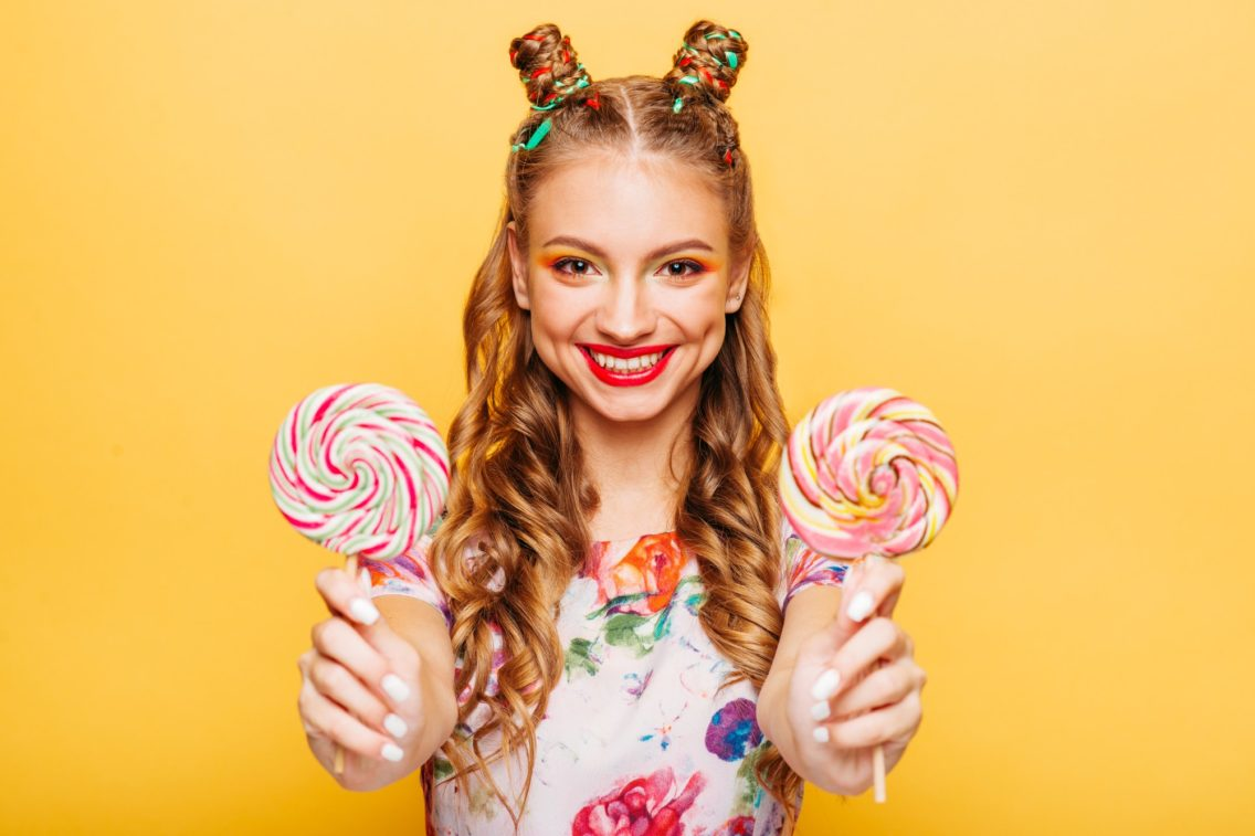 Smiling lady holding two huge colorful lollypops