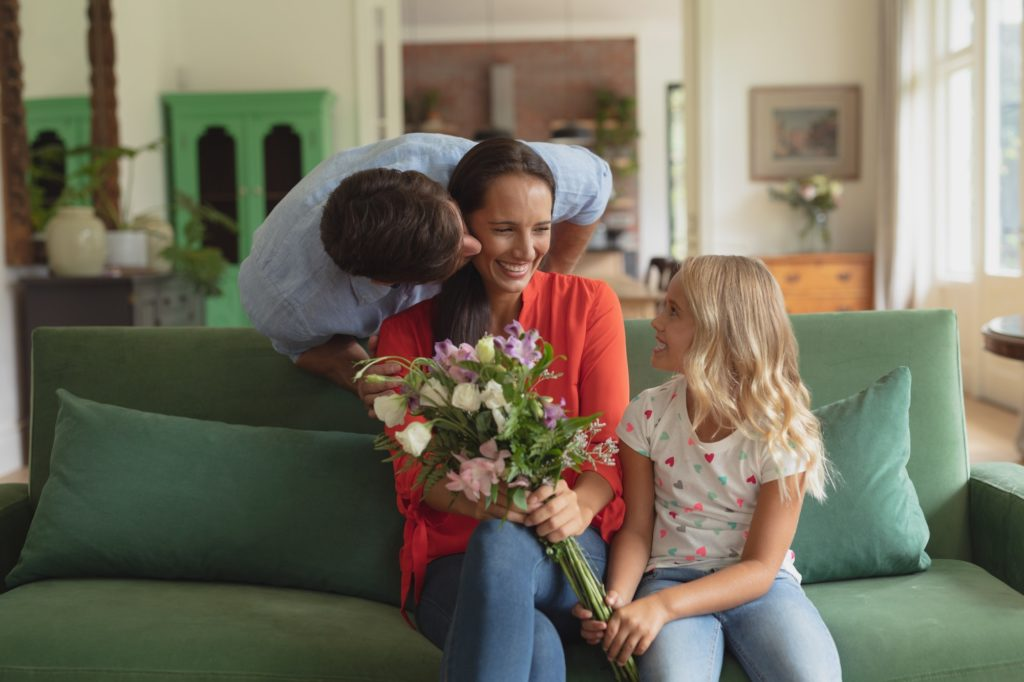 Caucasian daughter giving bouquet to mother while father kissing her in living room