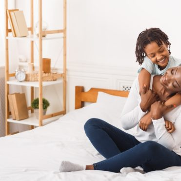 Full length image of black family in bedroom