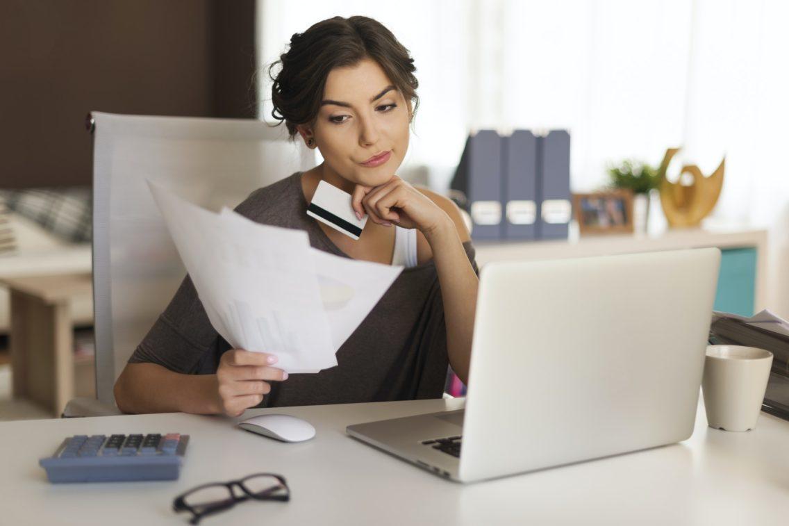 Pensive woman paying bills at home