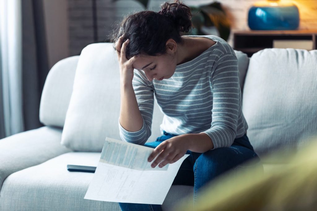 Worried young woman thinking about her problems while holding bills of home.